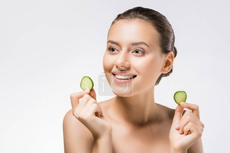 young smiling woman holding cucumber slices