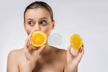 young woman with funny face expression and orange slices