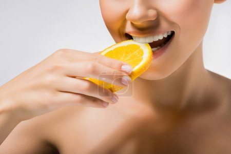 young woman holding and biting orange slice