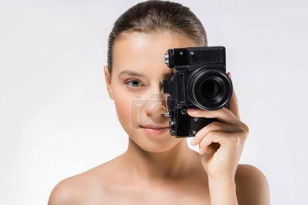 young woman hiding face behind black camera