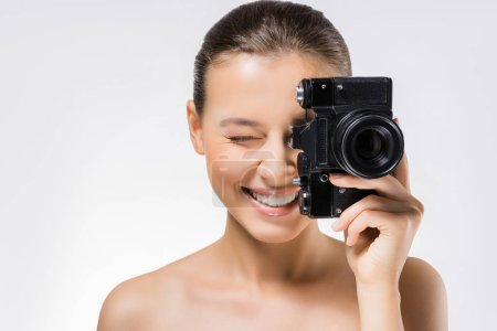 young woman with closed eye hiding face behind black camera