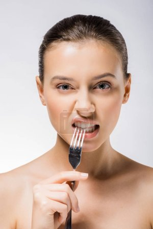 young beautiful woman holding silver fork near teeth