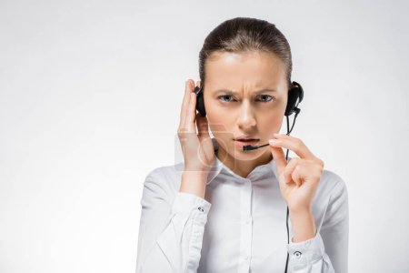 young serious call center operator touching headset