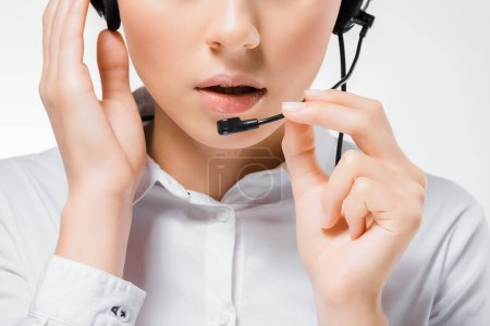 close up of young call center operator touching headset and speaking in microphone