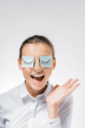 Photo for Young smiling woman with sticky notes on eyes and drawn eyelashes - Royalty Free Image