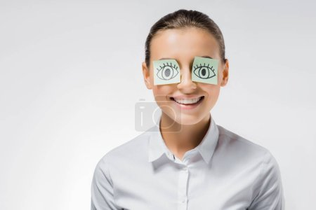 young smiling woman with sticky notes and drawn open eyes