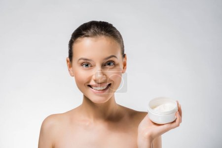 young beautiful woman holding white body cream