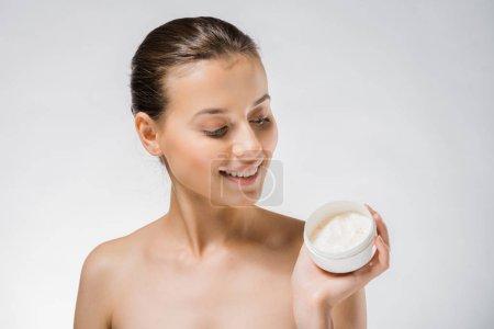 young beautiful woman holding white body cream