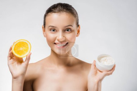 young beautiful woman holding white body cream and orange slice
