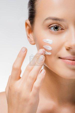 Photo pour Belle jeune femme appliquer blanche crème avec les doigts sur la joue - image libre de droit