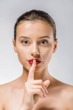 young beautiful woman with red lips showing silence symbol
