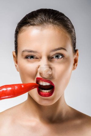 young beautiful woman with red lips biting chili pepper