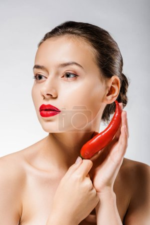 young beautiful woman with red lips holding chili pepper near face