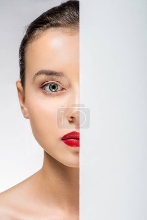 young woman hiding face behind white empty board