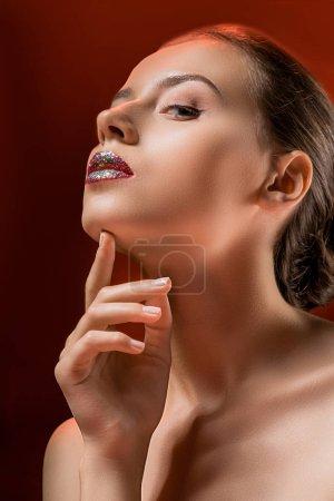 young beautiful woman with shiny lips touching chin on burgundy background