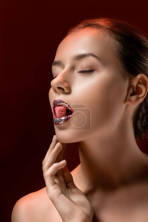 young woman with shiny lips and closed eyes holding pink candy in mouth on burgundy background