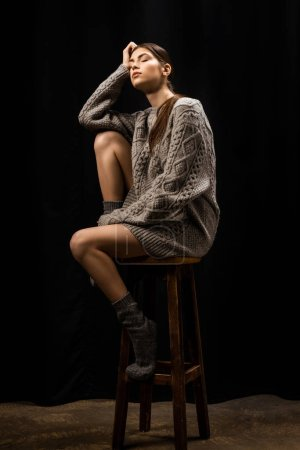 young thoughtful woman in woolen grey sweater and socks sitting on wooden bar stool on black background