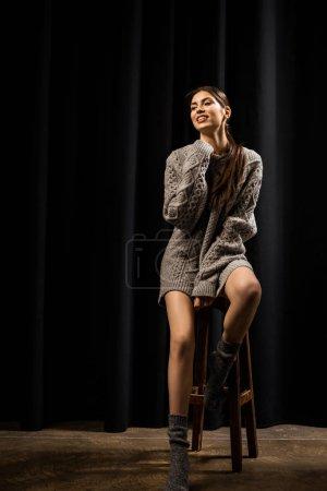 belle femme en laine gris pull et chaussettes assis sur tabouret de bar sur fond noir