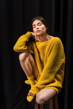 woman in yellow woolen sweater with eyes closed sitting on bar stool on black backdrop