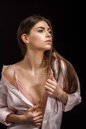 portrait of stylish young woman in pink underwear and shirt looking away isolated on black