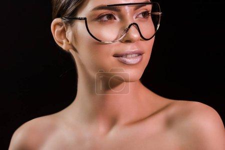 portrait of attractive young woman in fashionable eyeglasses with bare shoulders isolated on black
