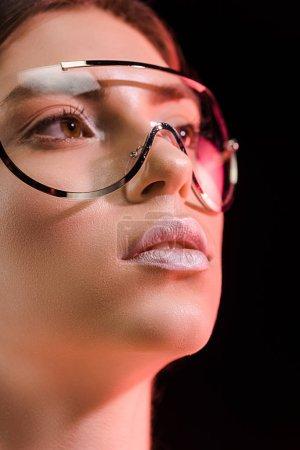 Foto de Retrato de hermosa mujer en moda gafas mirando a aislado en negro - Imagen libre de derechos