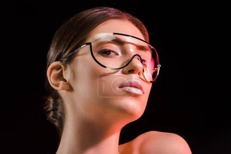 Foto de Retrato de hermosa mujer en moda gafas mirando a cámara aislada en negro - Imagen libre de derechos