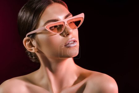 portrait of beautiful model in fashionable eyeglasses on dark background