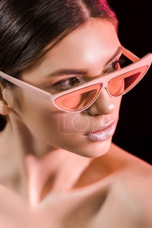 portrait of beautiful model in fashionable eyeglasses isolated on black