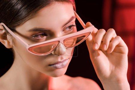 portrait of stylish model in eyeglasses posing on dark background