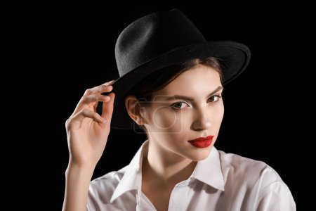 portrait of stylish woman in black hat and white shirt posing isolated on black
