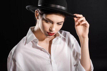 stylish young model with red lips in white shirt and black hat posing isolated on black