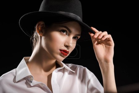 portrait of beautiful woman in white shirt and black hat posing isolated on black