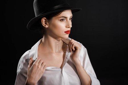 Photo pour Portrait de belle femme songeuse en chemise blanche et chapeau noir posant isolé sur noir - image libre de droit