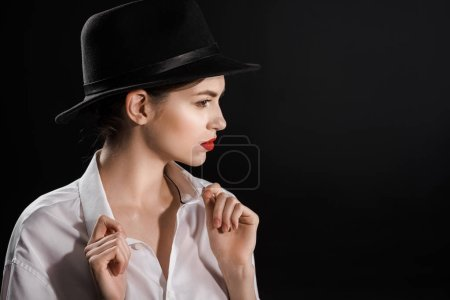 Photo for Side view of beautiful woman in white shirt and black hat posing isolated on black - Royalty Free Image