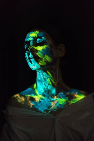 woman with ultraviolet paints on face posing on black background
