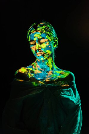 model with colorful neon paints on body posing on black backdrop