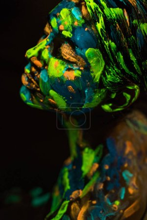 high angle view of woman painted with bright neon paints on black background