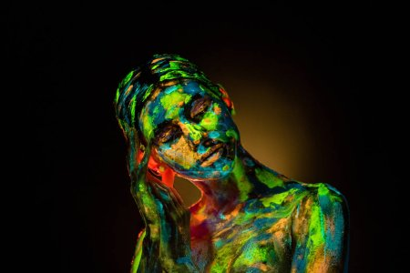 portrait of beautiful woman with colorful ultraviolet paints on body on black backdrop