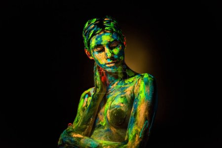 Photo for Portrait of beautiful woman with colorful ultraviolet paints on body on black backdrop - Royalty Free Image