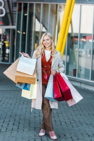 attractive smiling woman with sale tag holding shopping bags