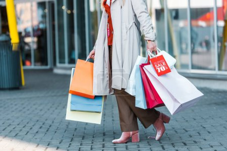 cropped view of woman with shopping bags and discount sign