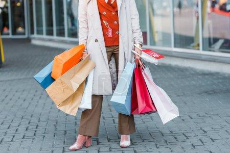 Photo pour Vue recadrée de shopaholic femelle avec sacs à provisions et panneau de réduction - image libre de droit