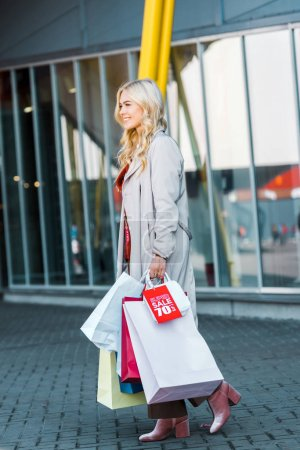 happy beautiful shopper with shopping bags and sale sign