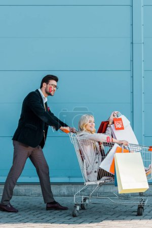 beautiful fashionable couple with shopping bags and sale tags having fun with shopping cart at blue wall