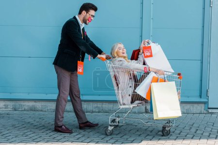 happy couple with shopping bags and sale tags having fun with shopping cart at blue wall