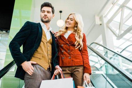 beautiful stylish couple with shopping bags standing on escalator