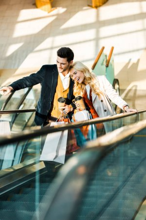 happy stylish man with coffee to go showing something to girlfriend with shopping bags standing on escalator
