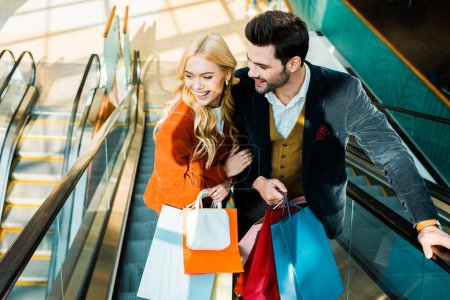 elegant smiling couple with shopping bags standing on escalator