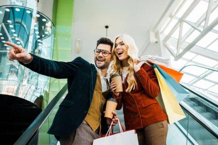 Photo pour Copain à la mode avec du café pour aller montrer quelque chose à petite amie excitée avec des sacs à provisions debout sur l'escalator - image libre de droit